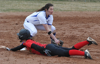 Troy Athens' Claire Smith dives back safely to third base as Rochester's Emily Morrow tries for the put out during the OAA Crossover doubleheader played on Tuesday April 10, 2018 at Rochester High School.  The teams split with Athens taking the first game 11-0 in 5 innings, and Rochester winning the nightcap 8-1.  (Oakland Press photo by  Ken Swart)