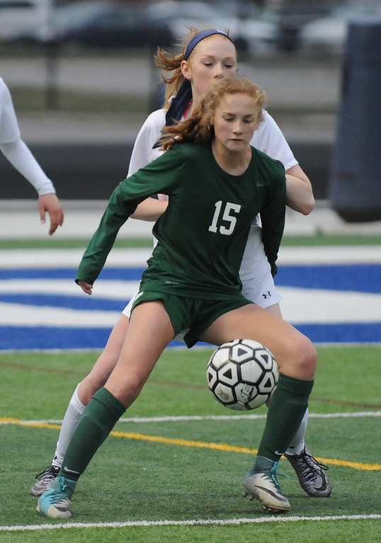 . Novi\'s Avery Fenchel (15) controls the ball in front of Rochester\'s Jessica Hegger during the match played on Friday April 13, 2018 at Rochester HS.   Fenchel had the Wildcats first goal to help the Wildcats defeate the Falcons 3-1. (Oakland Press Photo by Ken Swart)