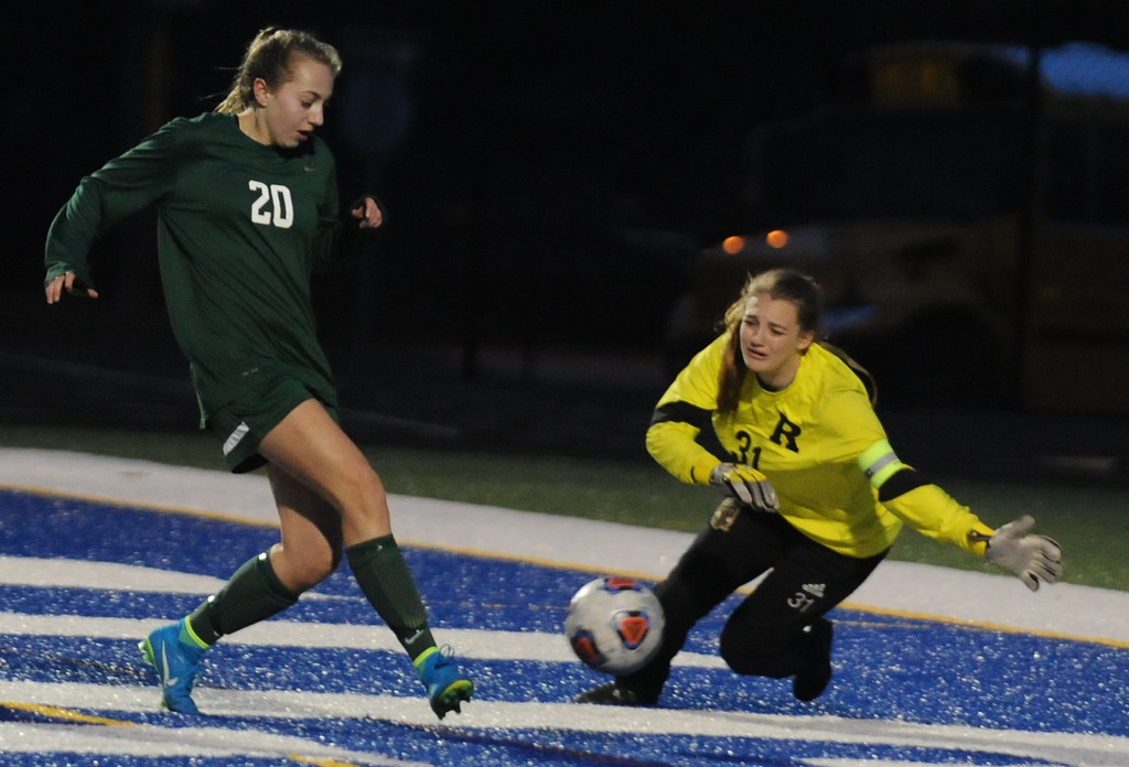 . Novi\'s Julia Stadtherr (20) puts in the game winning goal as Rochester goalkeeper Kaitlyn Godwin tries to make the save.  The Wildcats defeated the Falcons 3-1 in the match played on Friday April 13, 2018 at Rochester HS.  (Oakland Press Photo by Ken Swart)