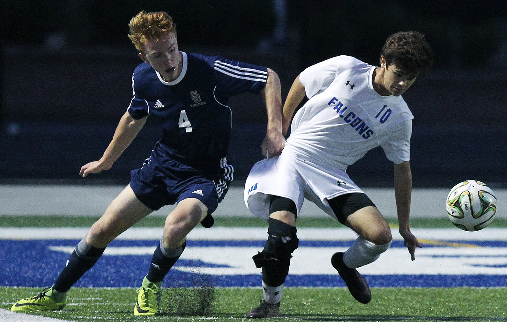 . Luciano Errecalde (10), Rochester, battles for ball possession with Nick Glazier (4), Rochester Stoney Creek, during varsity soccer action at Rochester High School Tuesday, Sept. 19, 2017. The Falcons defeated their cross town rival 3-0. (For The Oakland Press / LARRY McKEE)