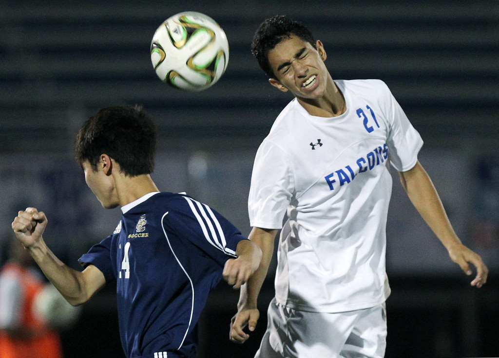 . Gabe Baylon (21), Rochester, makes a header pass over the head of Brandon Kim, Rochester Stoney Creek, during varsity soccer action at Rochester High School Tuesday, Sept. 19, 2017. The Falcons defeated their cross town rival 3-0. (For The Oakland Press / LARRY McKEE)