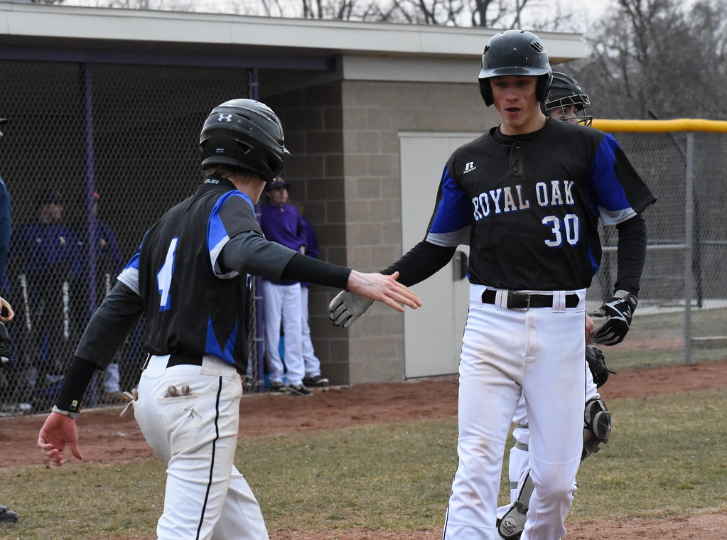 . Royal Oak\'s Rob DeBastos (30) is met at home plate by teammate Sam Perkey after both players scored on a RBI single by Matt Isaacson Friday in the Ravens\' 5-3 victory over Auburn Hills Avondale. (Photo gallery by Jason Schmitt/The Oakland Press)