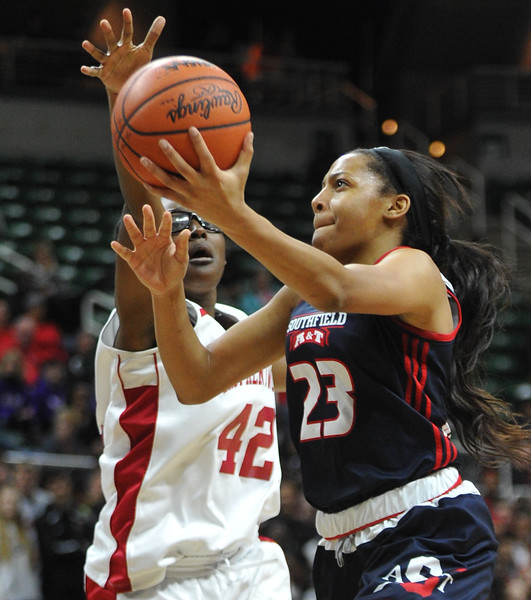 Southfield A&T's Deja Church (23) drives to the basket for 2 of her game high 26 points as East Kentwood's Corinne Jamison (42) defends during the MHSAA Class A State semi-final played on Friday March 17, 2017 at the Breslin Center in East Lansing.  The Warriors lost to the Falcons 55-51.  (MIPrepZone photo by Ken Swart)
