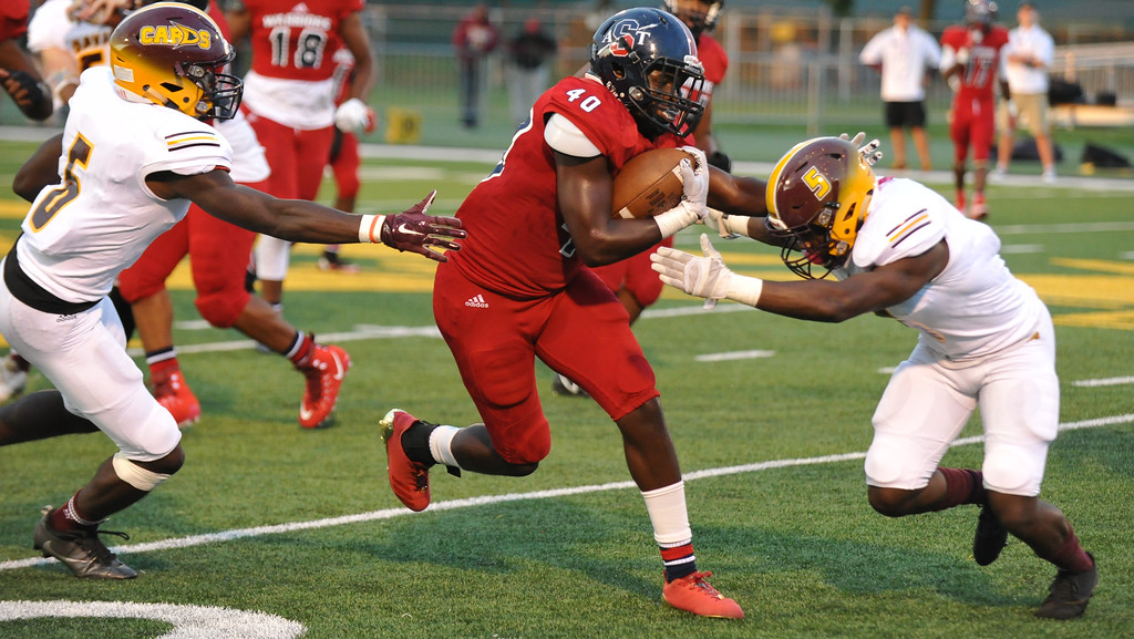 . Southfield A&T\'s Blake Grice-Brunson (40) splits the Davison defenders Anthony Fordham (L) and Carrington Terry (5) during the Xenith Prep Kickoff Classic game played on Thursday August 24, 2017 at Wayne State University. The Cardinals defeated the Warriors 56-54 in triple overtime.  (Oakland Press Photo by Ken Swart)