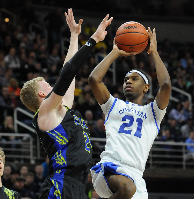 . Bryce Washington (21) of Southfield Christian puts up a short jumper over Buckley\'s Denver Cade during the MHSAA Class D State Title game played on Saturday March 24, 2018 at The Breslin Center in East Lansing.  The Eagles defeated the Bears 64-54 to win the state title.  (Oakland Press photo by Ken Swart)