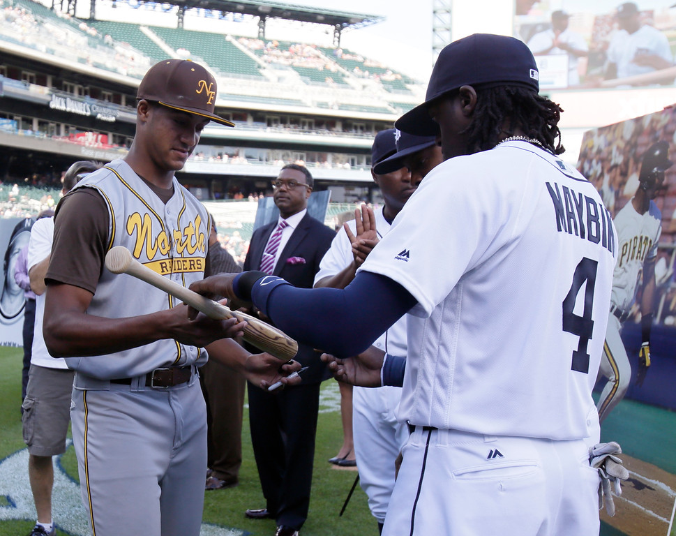 """. Alex Darden, from Farmington High School in Farmington, Mich., receives an autographed bat from Detroit Tigers\' Cameron Maybin (4) during the Tigers\' annual \""""Passing of the Bat Ceremony\"""" before their baseball game against the Chicago White Sox Friday, June 3, 2016, in Detroit. The ceremony is part of the Tigers\' Negro League weekend that celebrates the past, present and future contributions of African American ballplayers to the game of baseball. (AP Photo/Duane Burleson)"""