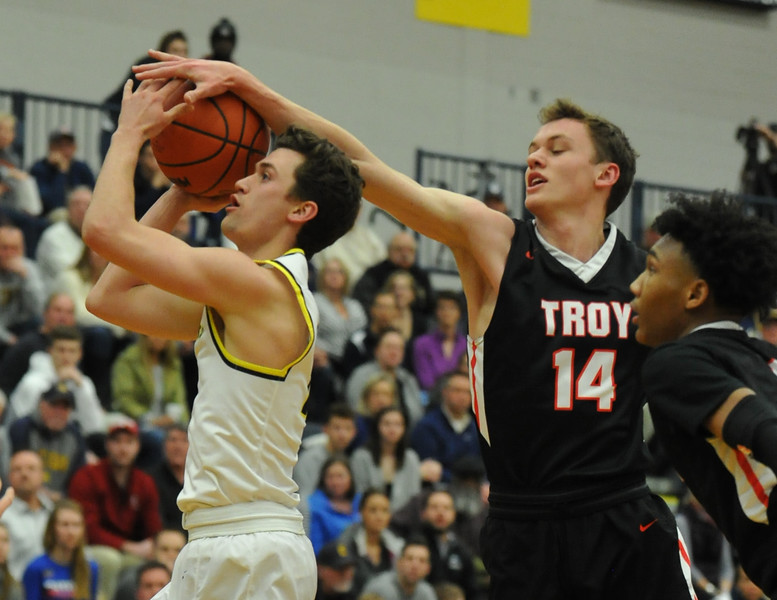 Troy's Jason Deitz (14) blocks the shot of Clarkston's Foster Loyer during the OAA Red matchup played on Friday February 15, 2018 at Clarkston High School.  The Colts lost to the Wolves 58-49. (Oakland Press photo by Ken Swart)