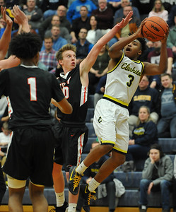 Clarkston's CJ Robinson (3) shoots an off balance jumper as Troy's Clay Sebastian defends during the OAA Red matchup played on February 15, 2018 at Clarkston High School.  The Wolves defeated the Colts 58-49. (Oakland Press photo by Ken Swart)