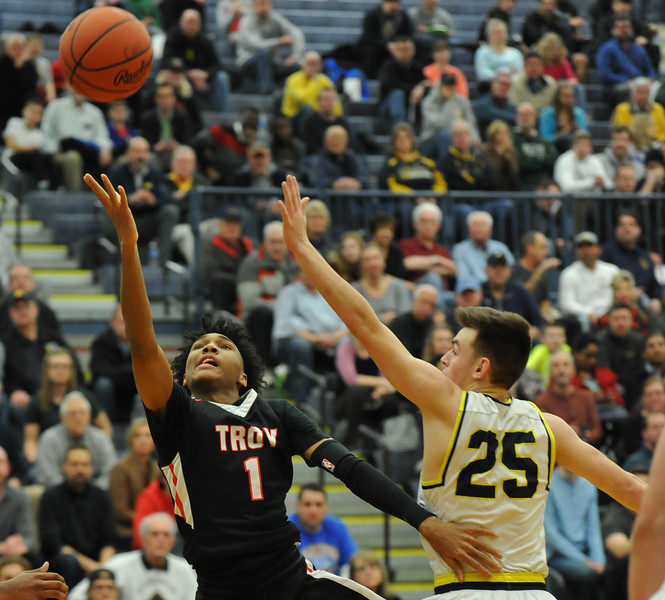 Leon Ayers (1) of Troy is puts up a runner down the lane as Clarkston's Nick Wells (25) defends during the OAA Red matchup played on Friday February 15, 2018 at Clarkston High School.  Ayers had a team high 17 points but the Colts lost to the Wolves 58-49. (Oakland Press photo by Ken Swart)