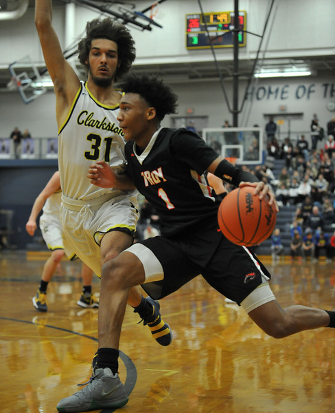 Leon Ayers (1) of Troy is guarded closely by Chase Wasilk (31) during the OAA Red matchup played on Friday February 15, 2018 at Clarkston High School.  Ayers had a team high 17 points but the Colts lost to the Wolves 58-49. (Oakland Press photo by Ken Swart)