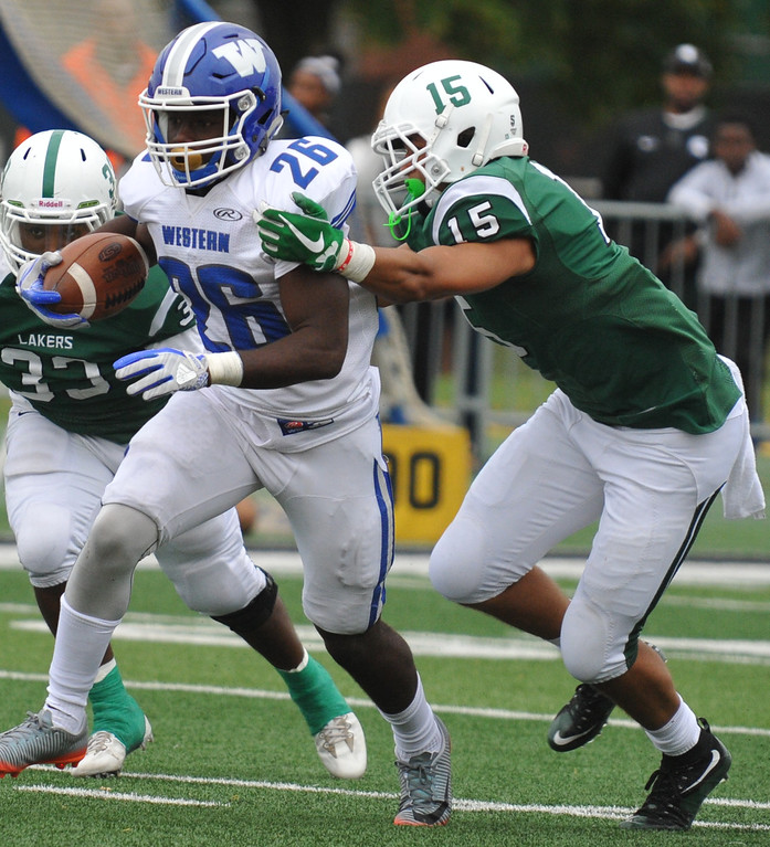 . Walled Lake Western�s Jakkell Moore-Wells (26) splits the West Bloomfield defenders Shamar Dennis (33) and James Faulkner (15) during the Xenith Prep Kickoff Classic game played on Thursday August 24, 2017 at Wayne State University.  The Warriors defeated the Lakers 19-14.  (Oakland Press photo by Ken Swart)