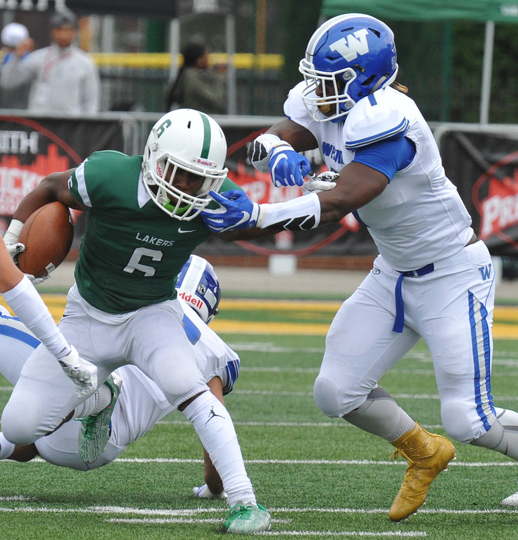 . Walled Lake Western�s Jonathon Moffett (R)) reaches for West Bloomfield�s Collin Heard (6) during the Xenith Prep Kickoff Classic game played on Thursday August 24, 2017 at Wayne State University.  The Warriors defeated the Lakers 19-14.    (Oakland Press photo by Ken Swart)