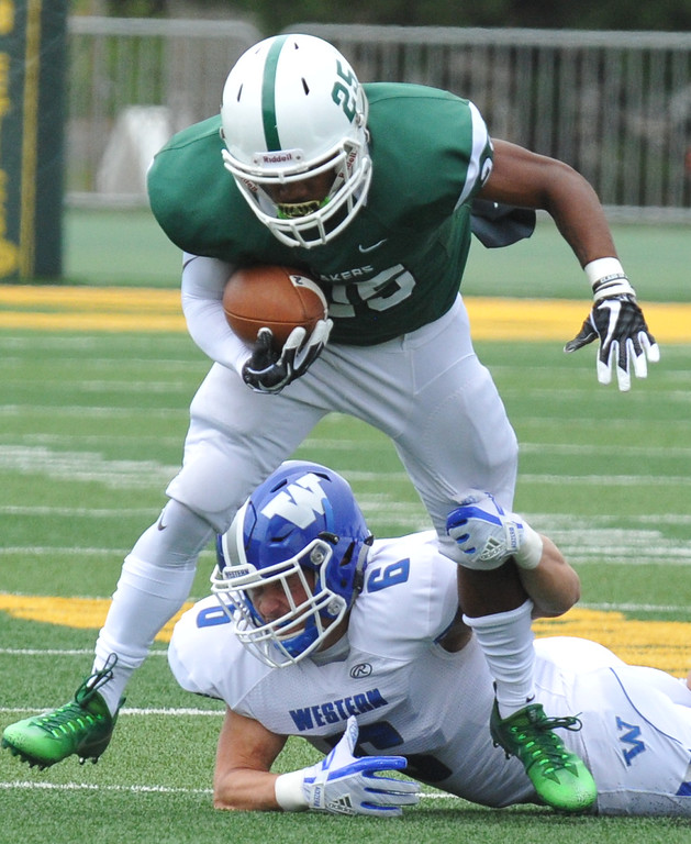 . West Bloomfield�s Jhordan Rush (25) is tripped up by Walled Lake Western�s Zak Kempster (6) during the Xenith Prep Kickoff Classic game played on Thursday August 24, 2017 at Wayne State University.  The Lakers lost to the Warriors 19-14.   (Oakland Press photo by Ken Swart)