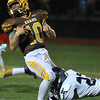 Rochester Adams quarterback Kyle Wood (10) is wrapped up by Waterford Mott's Pat Bicknell (22) during the MHSAA D1 Pre-district game played on Friday October 28, 2016 at Adams HS.  The Highlanders lost to the Corsairs 28-21.  (MIPrepZone photo by Ken Swart)