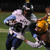 Waterford Mott's Colin McGrath (21) is brought down by Rochester Adams' John Filbin during the MHSAA D1 Pre-district game played on Friday October 28, 2016 at Adams HS.  The Corsairs won the game 28-21.  (MIPrepZone photo by Ken Swart)