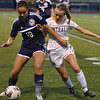 Waterford Mott's Kayla Sparre (18) tries to hold off Walled Lake Central's Kayla Quinn during the match played on Tuesday May 9, 2017 at WLC HS.  The Corsairs defeated the Vikings 3-1.  (MIPrepZone photo by Ken Swart)