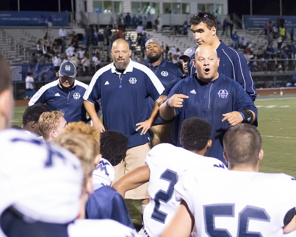 . An enthusiastic Waterford Mott head coach Chris Fahr addresses his team after the Cosairs upset Walled Lake Western 47-37 in Lakes Valley Conference action Friday night.  (Oakland Press photo by Timothy Arrick)