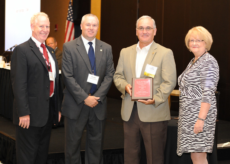 Ohio Rural Electric Cooperatives<br /> Annual Meeting<br /> August 11, 2015<br /> Co-op Owners for Political Action Leadership Award<br /> President's Club Century ACRE/OECPAC Plaque<br /> Pat O'Loughlin (OREC President and CEO), Marc Armstrong (OREC Director Government Affairs), Doug Comer (Logan County Electric Cooperative) and April Bordas (Ohio ACRE Chair).