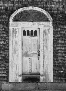 Door with fan detail, Friendship, Maine. This door has perfect proportions to my eye. The door is narrow, but has weight because of the side panels which are fitted to the width of the fan. The fan has fine fanning detail which compliment the delicate width of the door. The windows in the door top mimic the arch of the fan and draw the eye upward even more toward the fan. I don't know when this was built, but I'll guess very early 1800s.