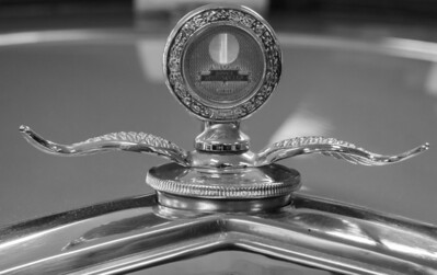 Chevy flying wheel hood ornament, Boyce Manometer Junior, black and white. Photo taken at http://www.vintageautomuseum.org/