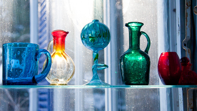 colored glass objects, window in my greenhouse, blue cup, orange and yellow flame glass pitcher, blue green swirled oil lamp, green pitcher, red, vase and bottle with marble in the top