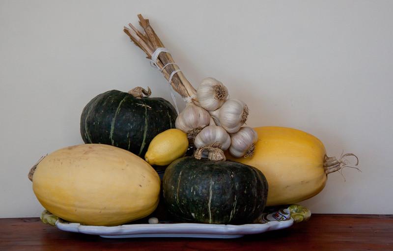 still life of winter and spaghetti squashes, lemon and braided garlic on Italian platter