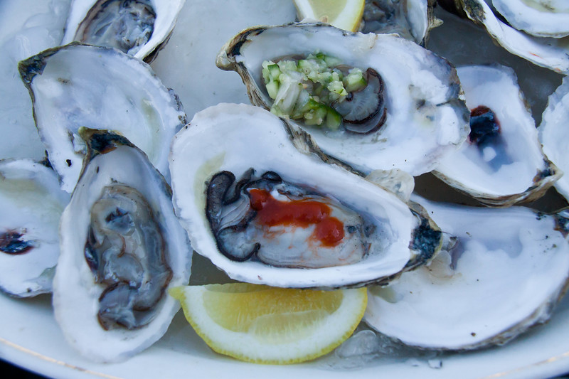 A platter of exquisite, Winterpoint oysters on the half shell. The oysters are kept cold sitting on crushed ice. They were served with lemon, Srirachia hot sauce and cucumber, onion mignonette. With white wine, they were fabulous! Locally harvested.