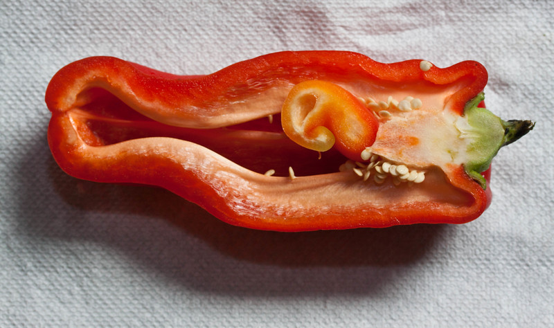 sweet, red Bell pepper sliced in half reveals and odd twist of seeds and internal membrane