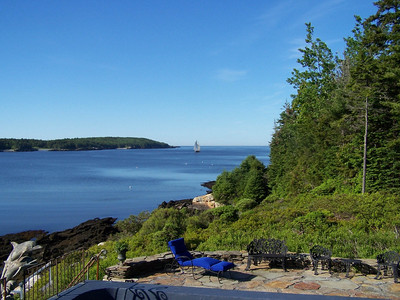 view from house looking south across Cape Small harbor and Hermit Island. Rim of saltwater swimming pool and patio visible in foreground.