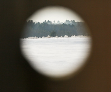 looking through a knot hole in a fence to a field beyond in January with hoar frost collecting on trees, Whitefield, Maine