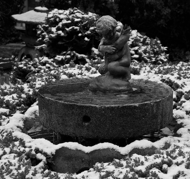 statuary of child holding fish with pagoda in the background, my coastal, Phippsburg, Maine garden in fresh snow. black and white,