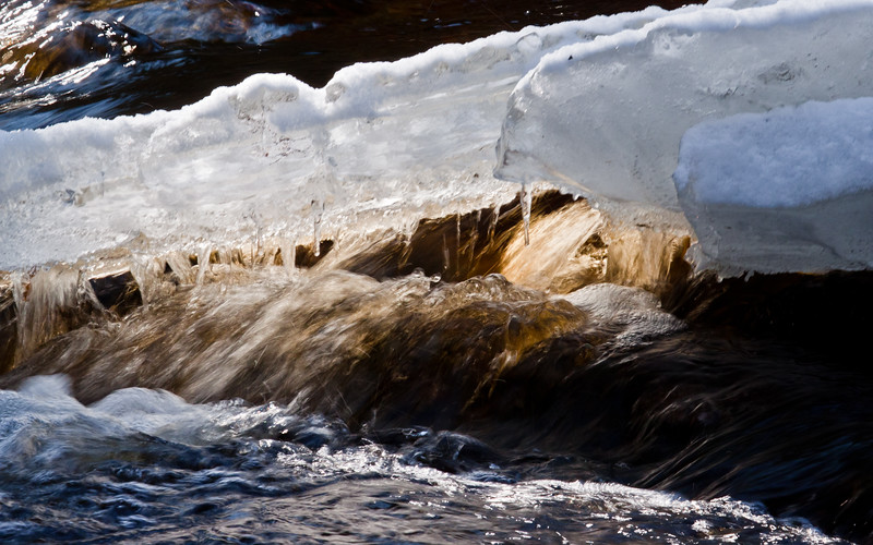 waters of creek rushing through ice and snow, winter scene, Phippsburg, Maine