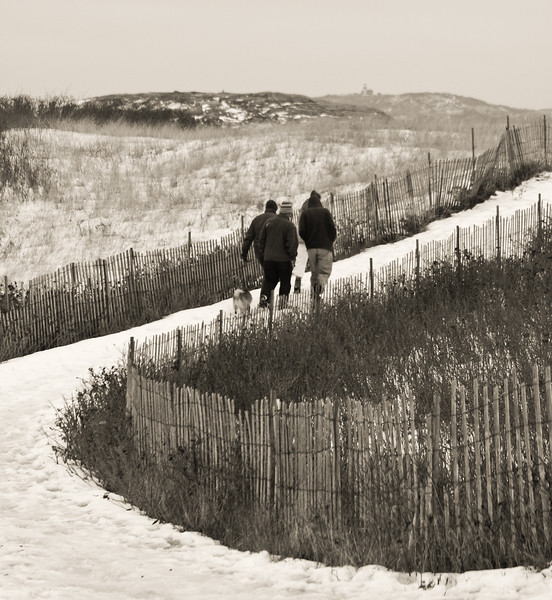 Friends walking with Pomeranian dog on snow covered path to the beach, Seguin Island Lighthouse in the background, Popham Beach State Park, Phippsburg, Maine, Winter scenic study in black and white. The park is open without admission fees in the winter. It is a place frequented by the hardy and otherwise winter bored.
