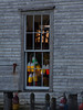 fishing wharf warehouse window with lobster buoys, Friendship, Maine