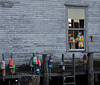 warehouse, wharf for commercial fishing in Friendship, Maine, with buoys in the window and pilings on wharf. Classic, historic fishing