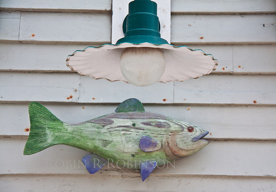 Carved fish sculpture, architectural, decorative detail with antique lamp fixture, Stonington, Maine
