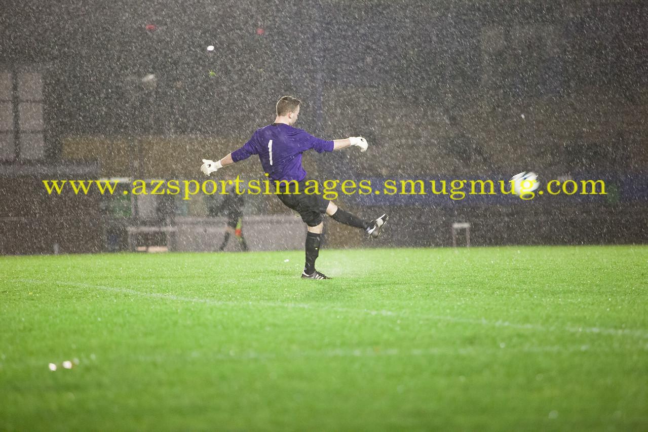 Southend Manor FC's Lawrence Priddle drop-kicks as the heavy rain come down