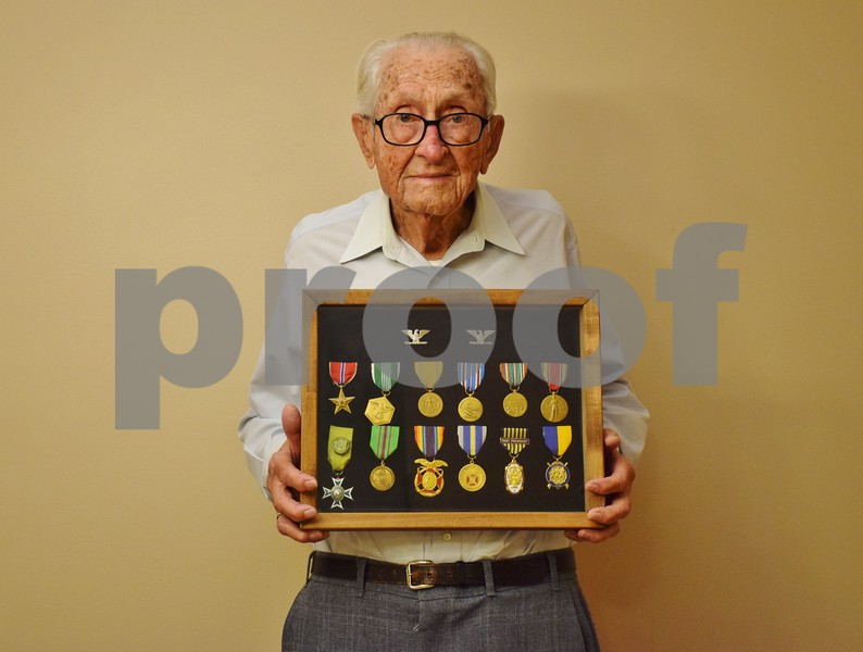 World War II veteran, 104-year-old Charles Long of Sycamore, holds awards he has received over the years for his military service.