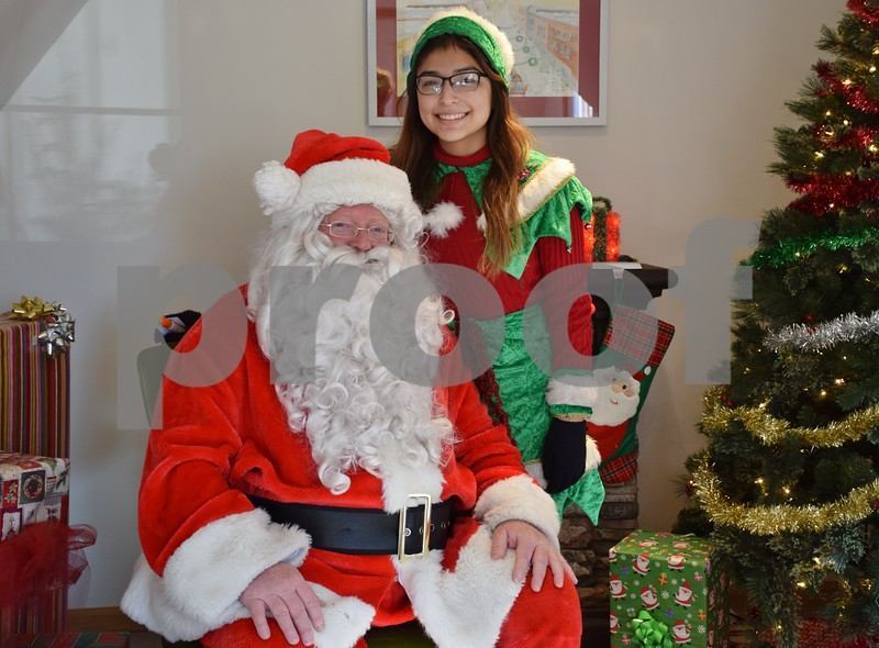 Santa Claus poses with Elf Susie Oliveros at his house on the DeKalb County Courthouse lawn in Sycamore.