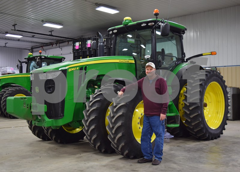 Tracy Jones of Kirkland poses with a tractor on his family farm on March 9.