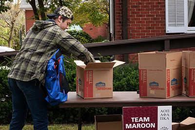 A student adds a donation to Team Maroon during Homecoming Week's Pack the Pantry event and competition. photo by: Ellee Achten