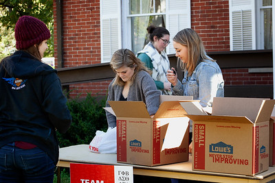 Maggie Wolf (center) and other volunteers for Homecoming week's Greek life Pack the Pantry event collect their first donation, counting each can with a hand held tally counter. photo by: Ellee Achten
