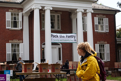 An OU student glances at the Pack the Pantry event set up on the front lawn of the Konneker Alumni Center. photo by: Ellee Achten