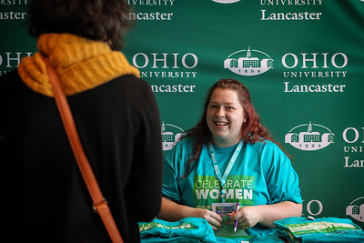A volunteer for the 13th Annual Celebrate Women Conference folds colorful event t-shirts and chats with attendees.