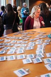 A woman looks for her name among the ID lanyards prepared for the attendees of the 13th Annual Celebrate Women Conference on March 22, 2019.
