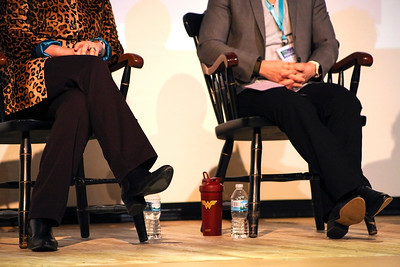 A travel tumbler emblazoned with the Wonder Woman symbol sits on the floor between panelists during the moderated discussion at the 13th Annual Celebrate Women Conference on March 22, 2019.