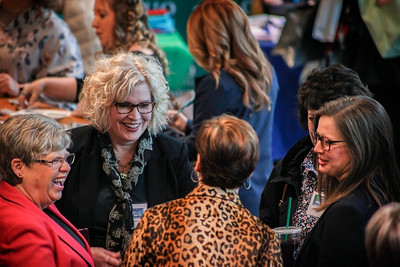 Laurie Sheridan Lach (left-center)--moderator for the morning panel and discussion--catches up with other attendees of the 13th Annual Celebrate Women Conference greet each other during the registration and networking hour on March 22, 2019.