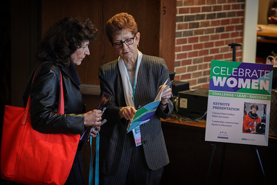 A sign showing this year's keynote speaker for the 13th Annual Celebrate Women Conference is positioned outside the main auditorium, while attendees discuss the day's schedule.