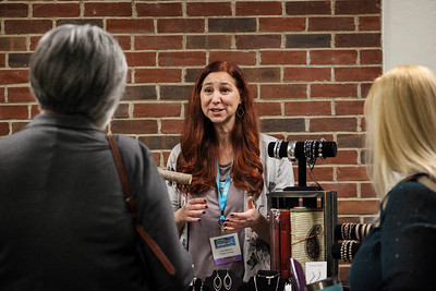 Lisa Gillispie explains the decorative wares at her table for Trades of Hope, to attendees of the OU-Lancaster Celebrate Women Conference on March 22, 2019.