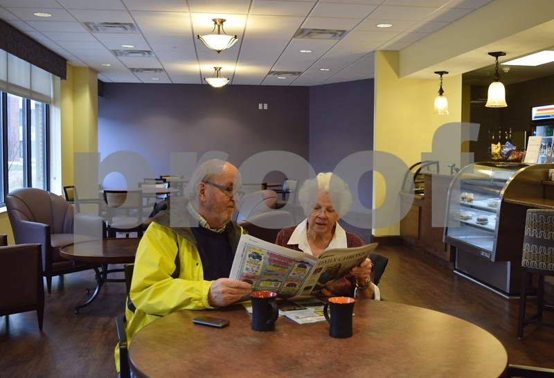 Dick and Karen Sjolund, residents of Oak Crest DeKalb Area Retirement Center in DeKalb, enjoy cups of coffee and read the newspaper together in the center's new bistro. The couple moved into their new apartment in The Oaks less than two weeks ago.